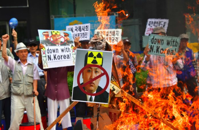 "South Korean conservative activists set fire to a portrait of North Korean leader Kim Jong-Un during a protest denouncing North Korea's nuclear test in Seoul on September 10, 2016. South Korean newspapers sounded the alarm on September 10 over what one termed the ""nuclear maniac"" Kim Jong-Un, saying the North Korean leader's fifth and biggest nuclear test is a game-changer demanding a tougher response. / AFP PHOTO / JUNG YEON-JE"