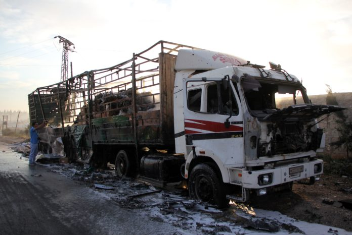 A damaged truck carrying aid is seen on the side of the road in the town of Orum al-Kubra on the western outskirts of the northern Syrian city of Aleppo on September 20, 2016, the morning after a convoy delivering aid was hit by a deadly air strike. The UN said at least 18 trucks in the 31-vehicle convoy were destroyed en route to deliver humanitarian assistance to the hard-to-reach town. / AFP PHOTO / Omar haj kadour