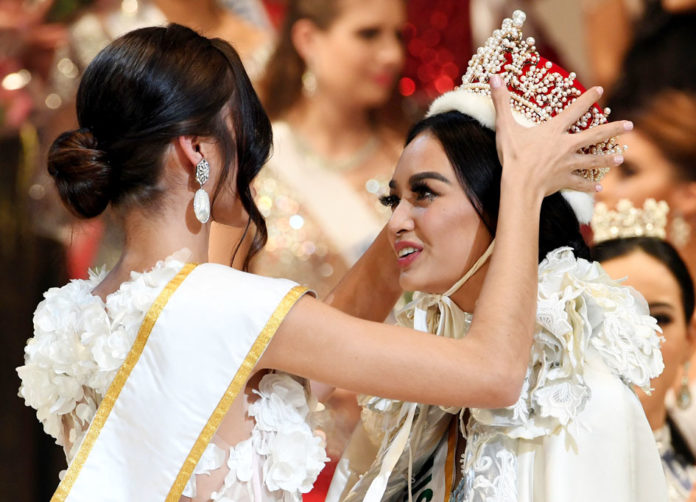 Newly elected 2016 Miss International Kylie Verzosa from Philippines (R) is helped by 2015 Miss International Edymar Martinez from Venezuela (L) during the Miss International beauty pageant final in Tokyo on October 27, 2016. / AFP PHOTO / TOSHIFUMI KITAMURA