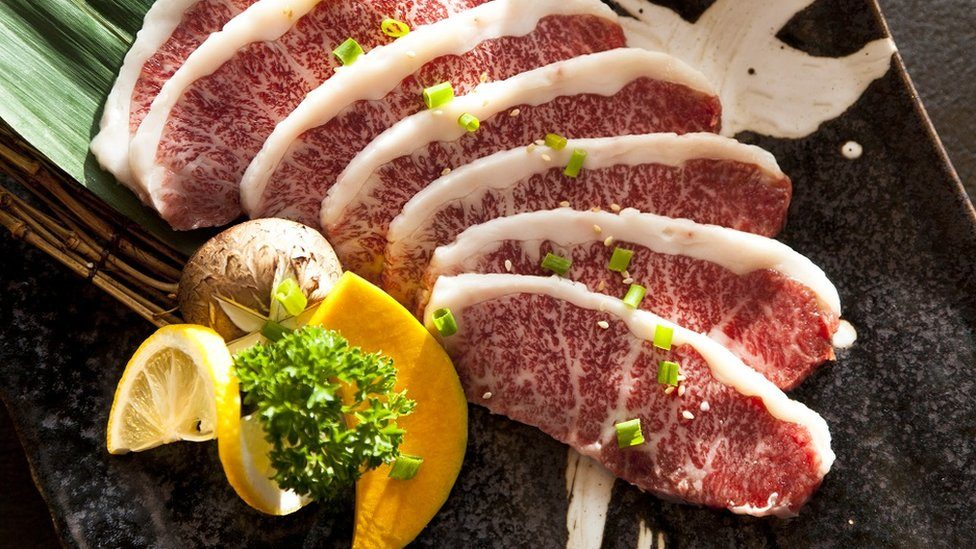 Wagyu Beef sliced decorated with a slice of lemon, on a plate on table