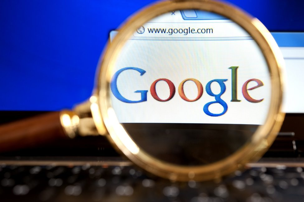 Close up to Google website through a magnifying glass on the laptop.