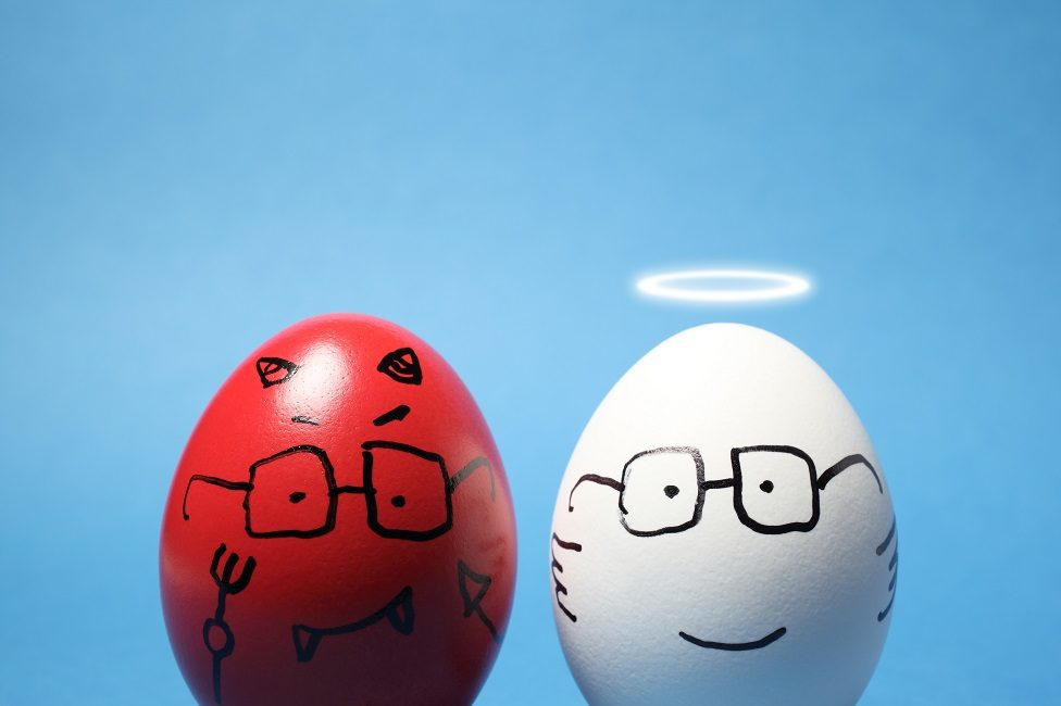 """Close-up of """"evil"""" and """"angel"""" eggs, against blue background."""
