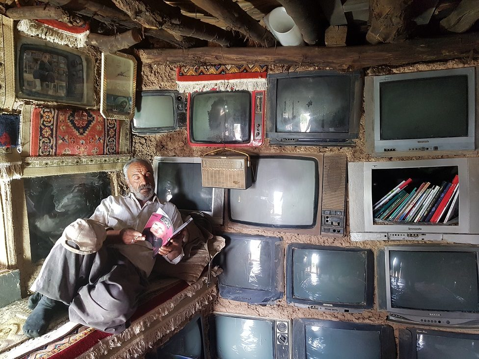 A man reading in his home next to a wall embedded with televisions