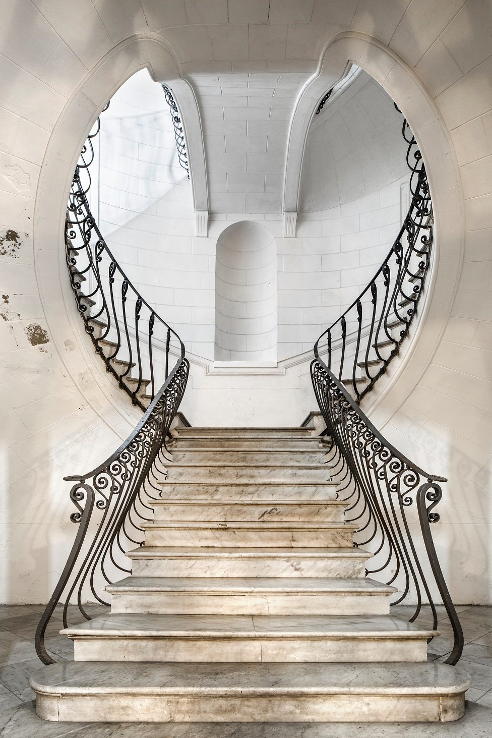 An ornate staircase of white stone and marble