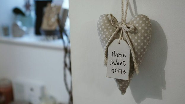 A heart-shaped trinket saying 'home sweet home' hangs from a door in Alex's family home