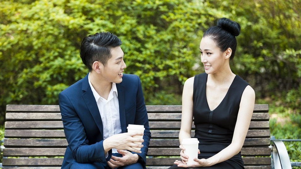A young couple having coffee on a park bench.