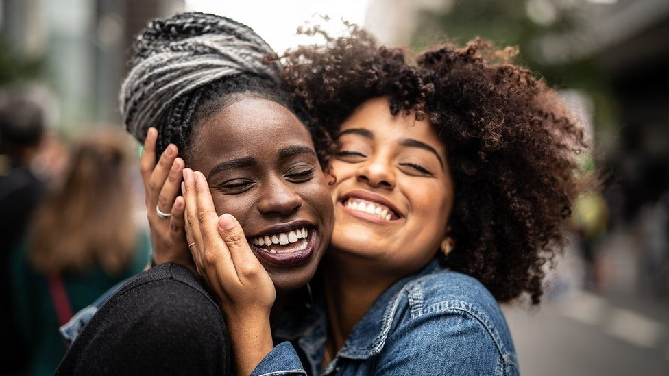 Two young women, best friends, smiling and hugging on the street.