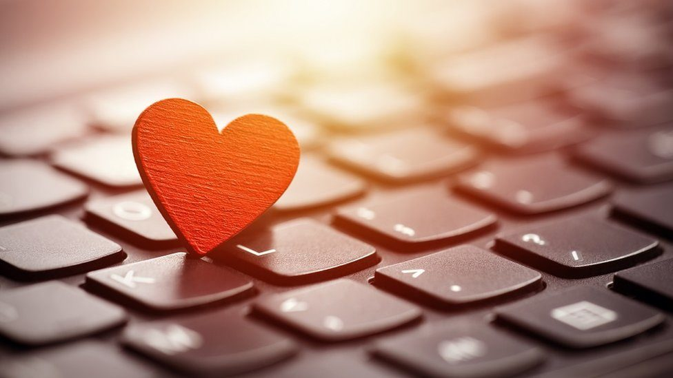 Concept image: a red heart on a computer keyboard.