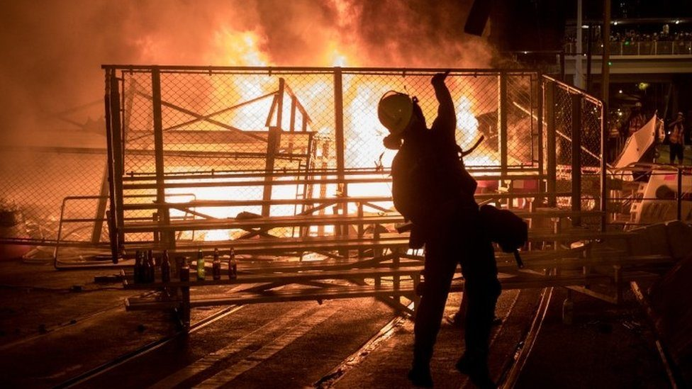 A protester throws a bottle onto a burning barricade in Hong Kong. Photo: 31 August 2019