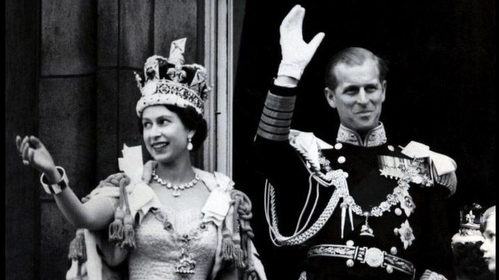 1953: Britains Queen Elizabeth II wears the Imperial State Crown as she and her husband, the Duke of Edinburgh - dressed in the uniform of Admiral of the Fleet - wave from the balcony of Buckingham Palace to the crowds after the Coronation.