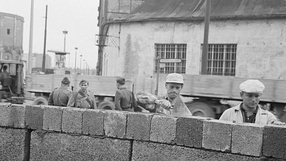 This picture shows East German workers building the Berlin wall in 1961, while being watched by communist police