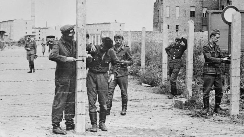 This picture from 14 August 1961 shows soldiers putting up a barbed wire barrier in preparation for the full construction of the Berlin Wall