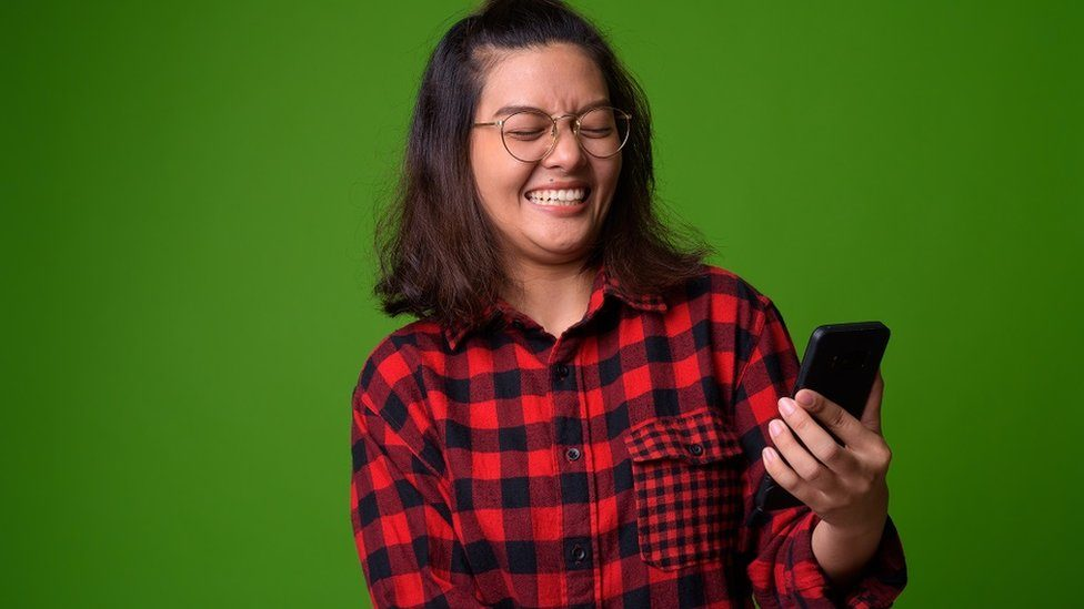 Young woman with a checked red and black shirt. She's laughing and holding a smarphone. Bright green background.