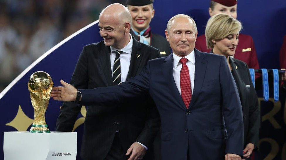 Putin gesturing at the World Cup trophy