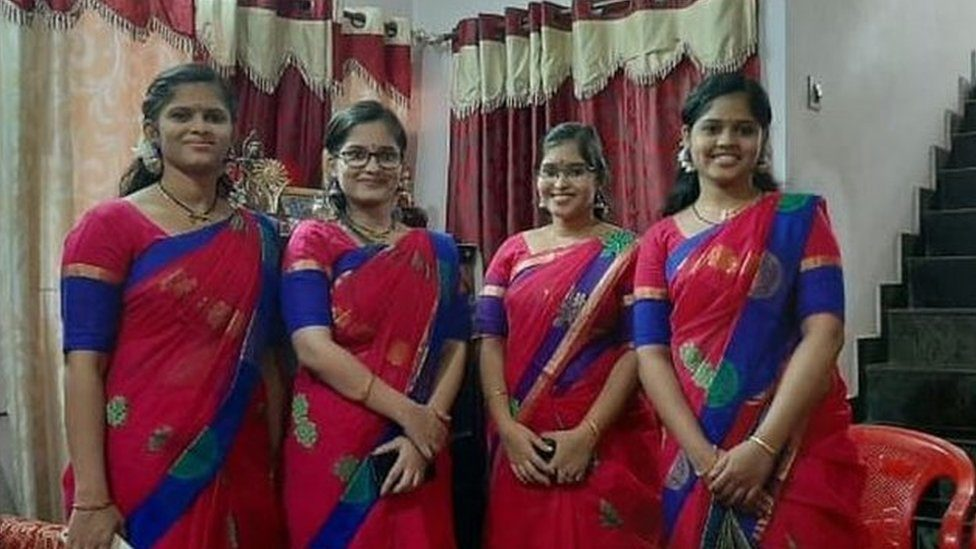 The four non-identical sisters posing for a photo