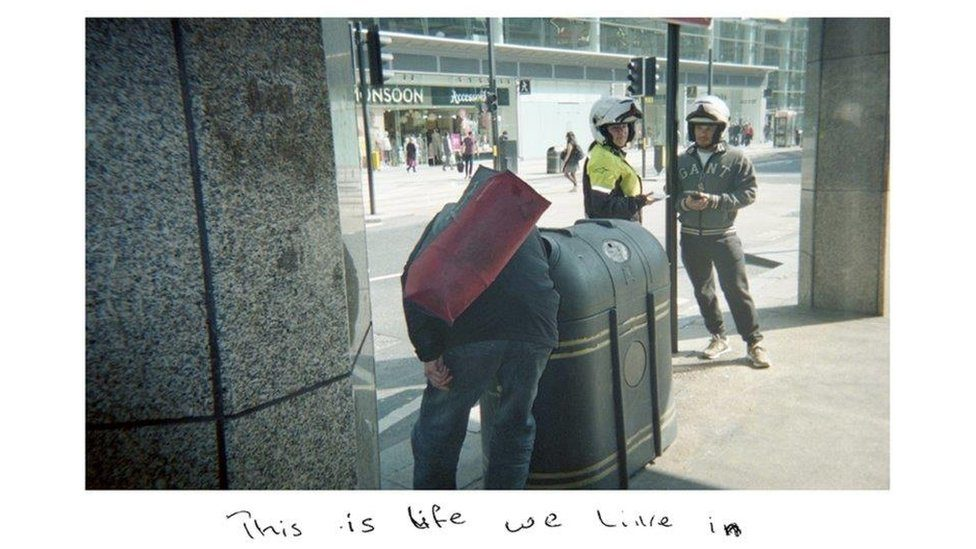 "One of Sunny's snapshots showing a homeless man rummaging in a bin, with the handwritten title: ""This is life we live in."""