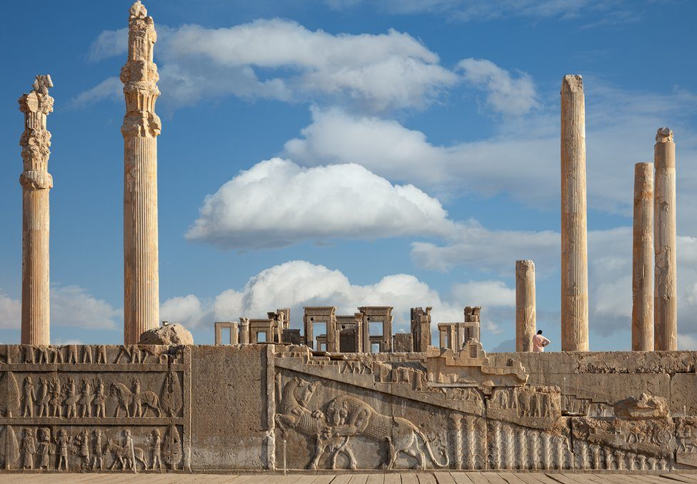 Ruins of Apadana and Tachara Palace behind stairway with bas relief carvings in Persepolis Unesco World Heritage Site against cloudy blue sky in Shiraz, Iran
