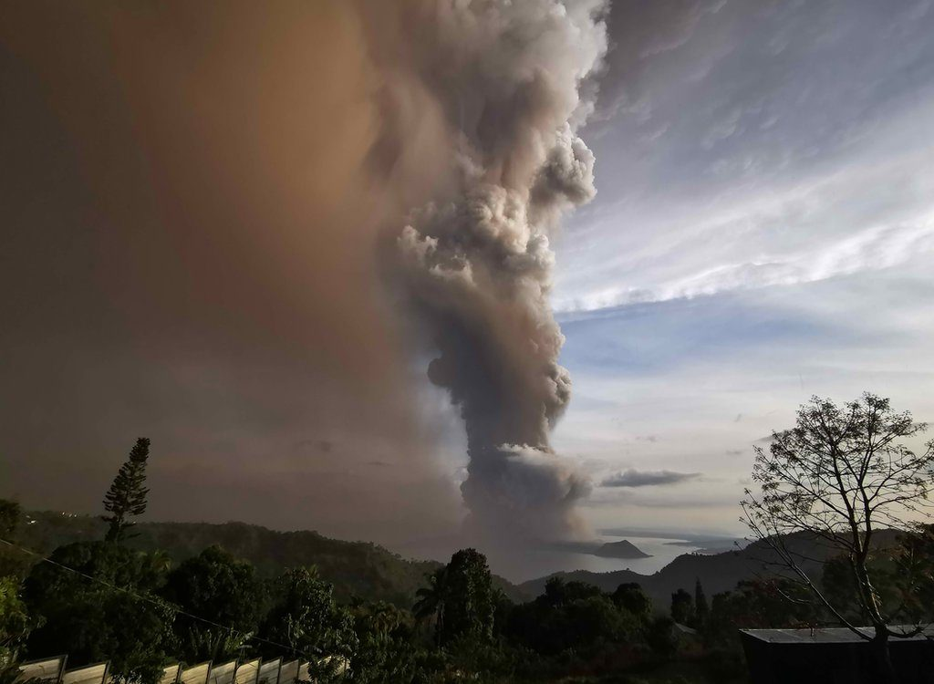 An ash column from erupting Taal Volcano looms over Tagaytay city, Philippines, 12 January