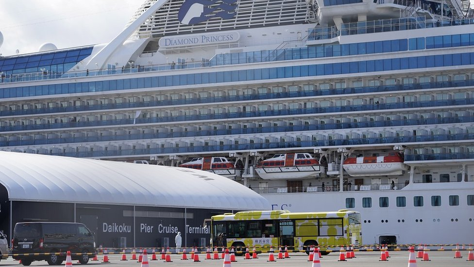 A bus is parked outside the Diamond Princess cruise ship docked at the Daikoku Pier Cruise Terminal in Yokohama, south of Tokyo, Japan, 19 February 2020
