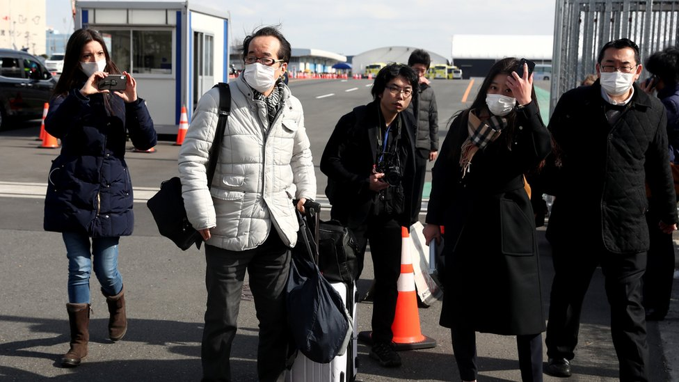 Passengers wearing face masks walk out from the Diamond Princess on February 19, 2020