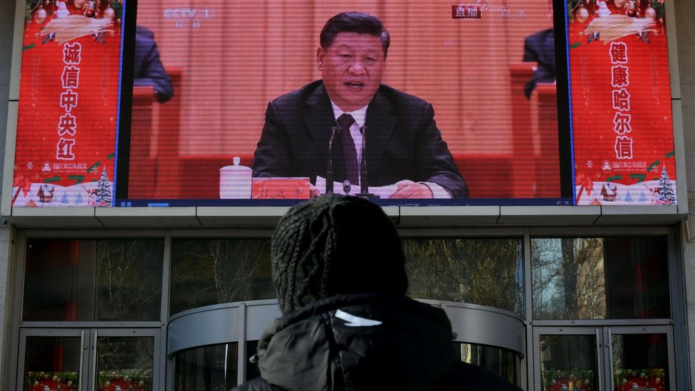"man stands and watches a large screen during President Xi Jinping""s speech at a grand gathering to celebrate the 40th anniversary of China""s reform and opening-up in Beijing on December 18, 2018 in Harbin, China"