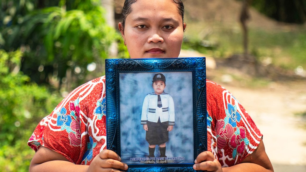 Purwanti with a photo of her daughter who drowned in an abandoned pit