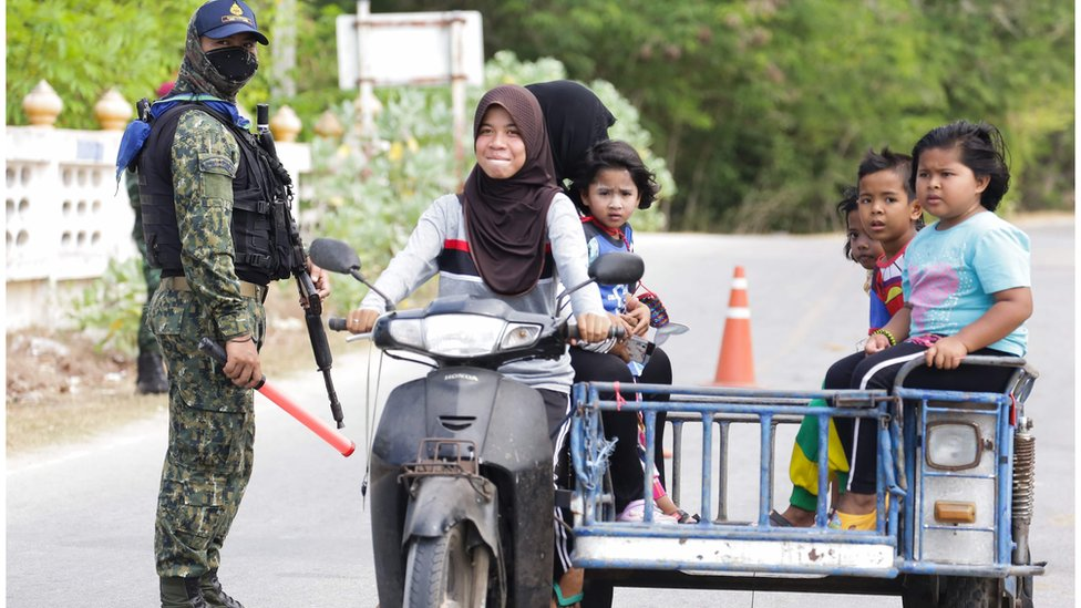 """An armed security personnel wearing a face mask guards a road check point in Nong Chik district to screen motorists and people returning from Malaysia in Thailand""""s southern province of Pattani on March 24, 2020"""