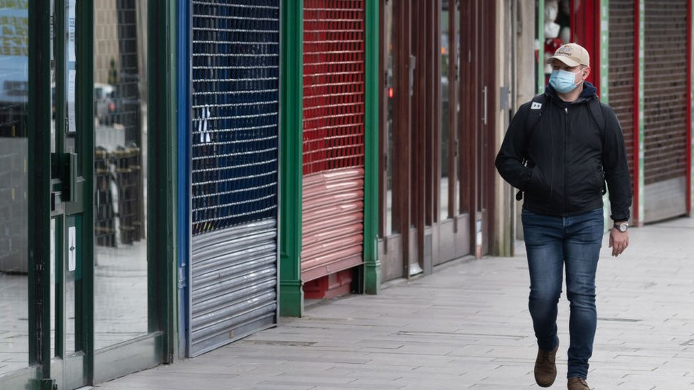 A man walking past closed shops