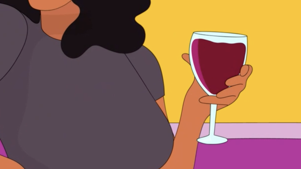 A woman holds a glass of wine while chatting
