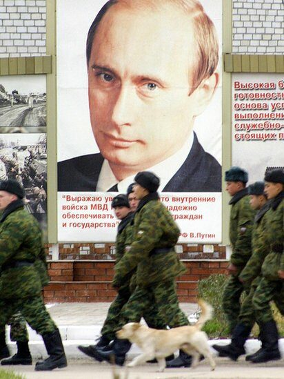 Russian soldiers march next to a giant poster of the Russian President Vladimir Putin at an army barrack in Grozny, Chechnya