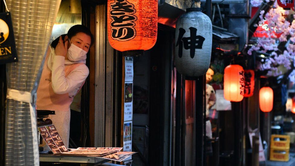 A woman wearing a face mask looks out from a yakitori restaurant in a traditional dining area on March 19, 2020 in Tokyo, Japan.