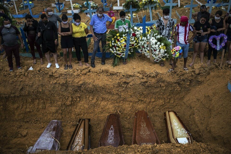 People attend a funeral at a mass grave at the Nossa Senhora Aparecida cemetery in Manaus, Brazil, 23 April 2020
