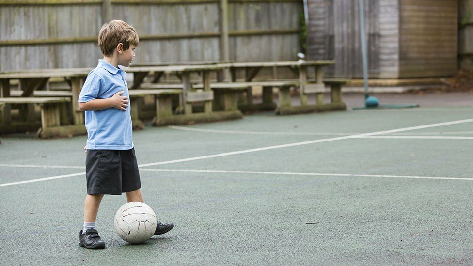 School boy playing on his own in playground