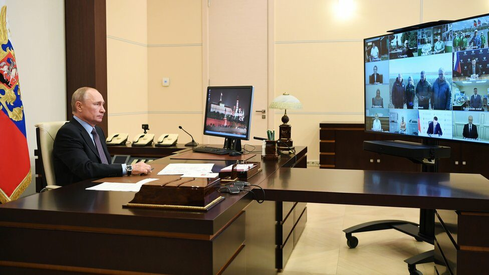 Russian President Vladimir Putin faces a TV screen with a number of officials on a video conference