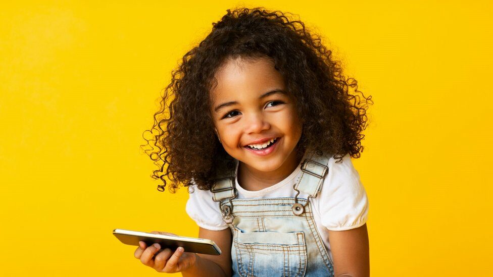Young black girl holidng a mobile phone