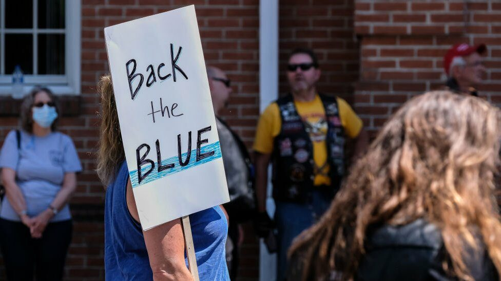 A woman holds a 'Back the Blue' placard during a pro-police rally.