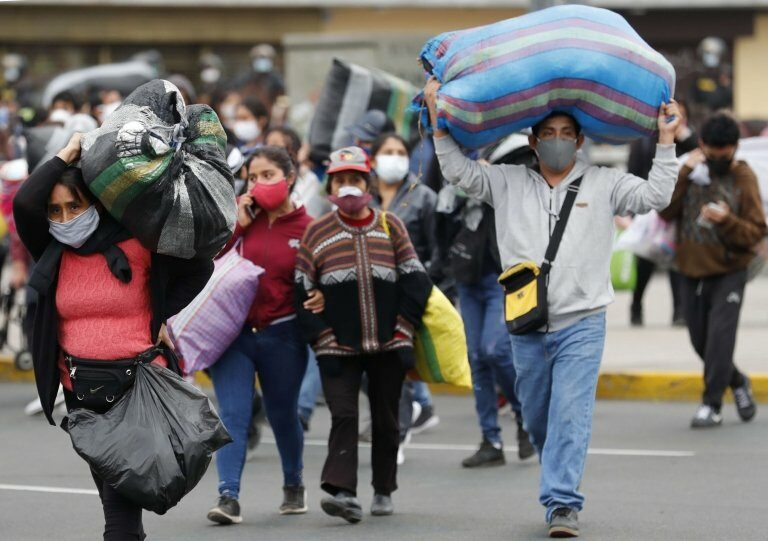 Street vendors move after being evicted by the Police from a public street where they sell their products, in downtown Lima, Peru, 12 June 2020