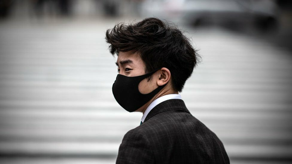 A man wearing a face mask waits to walk over Shibuya crossing on May 25, 2020 in Tokyo, Japan.