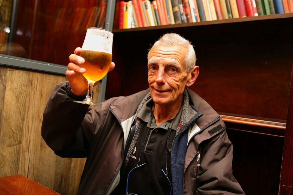 A man holds his pint of beer up to the camera
