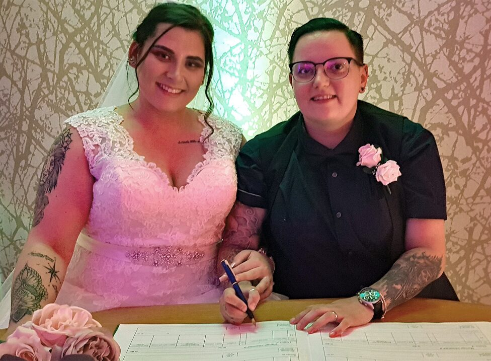 A wedding couple sign their marriage certificate