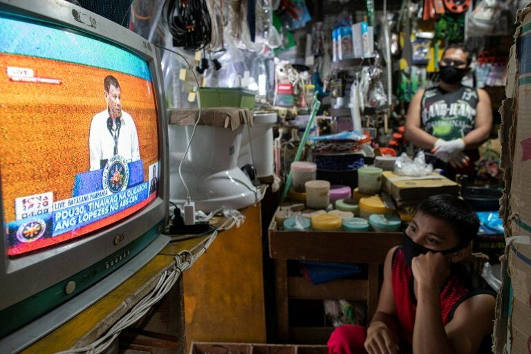 """Filipinos watch President Rodrigo Duterte""""s fifth State of the Nation Address from a television in a hardware store in Quezon City, Metro Manila, Philippines, July 27, 2020"""