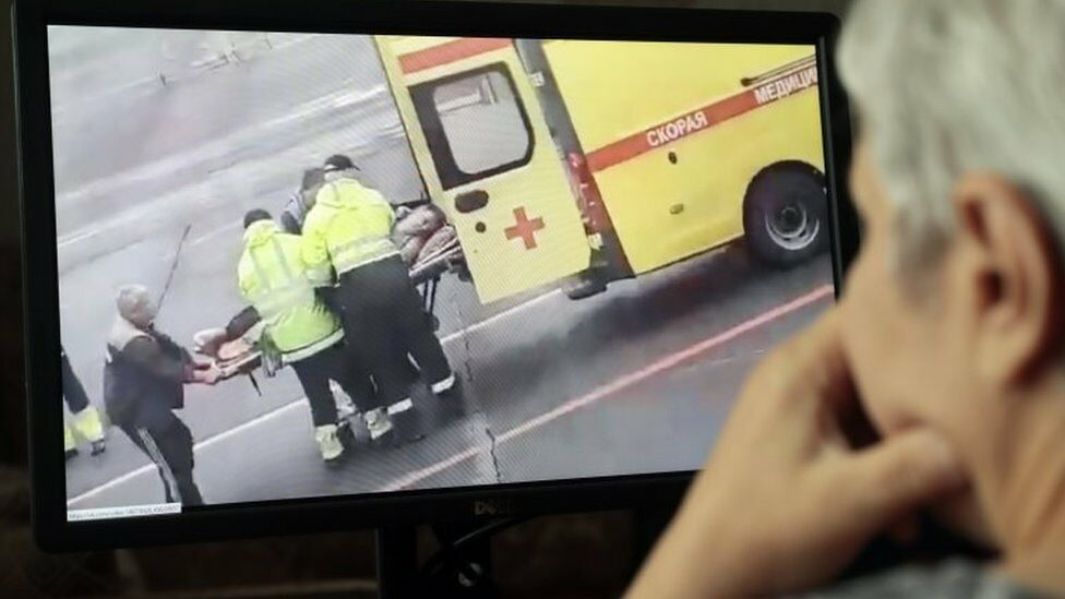 A man in Moscow watches social media footage of Mr Navalny being stretchered to an ambulance