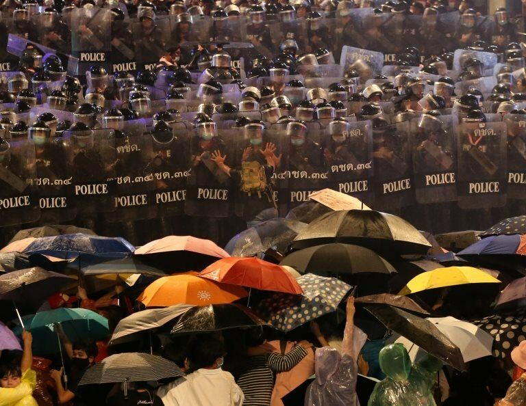 Pro-democracy protesters face riot police during an anti-government protest in Bangkok, Thailand, 16 October 2020