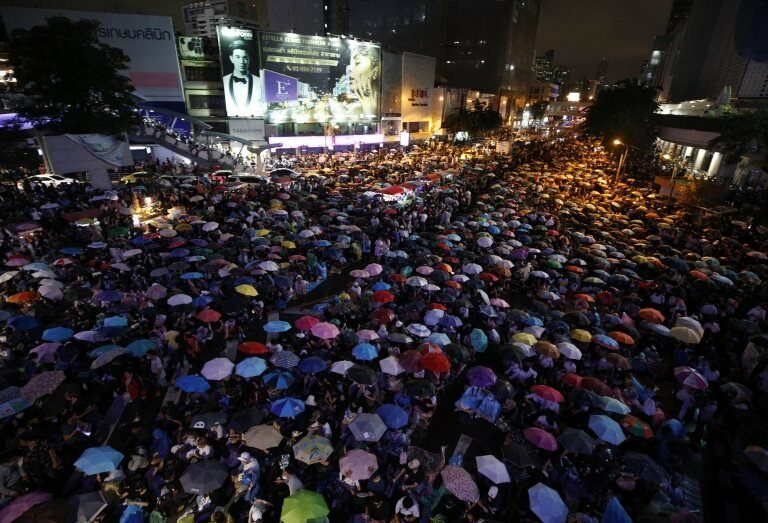Pro-democracy protesters with umbrellas to protect themselves from the rain attend an anti-government protest at intersection on the main road in Bangkok, Thailand, 16 October 2020.