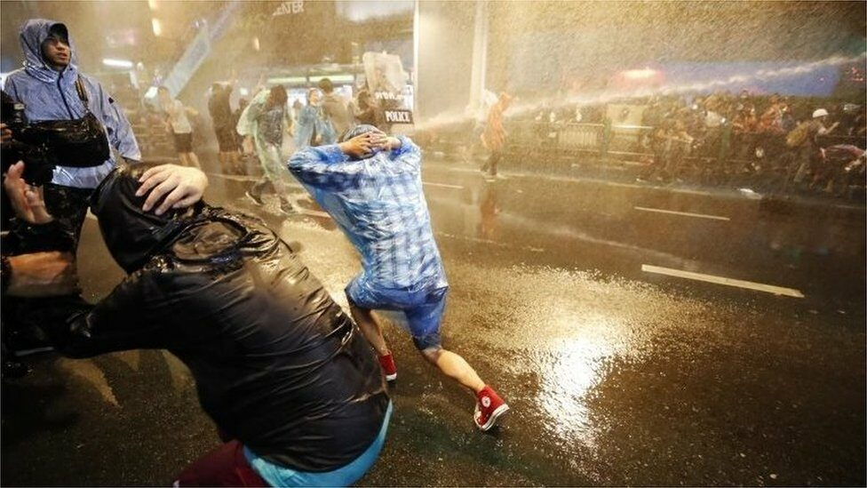 Pro-democracy protesters react as riot police fire water canons during an anti-government protest in Bangkok, Thailand, 16 October 2020