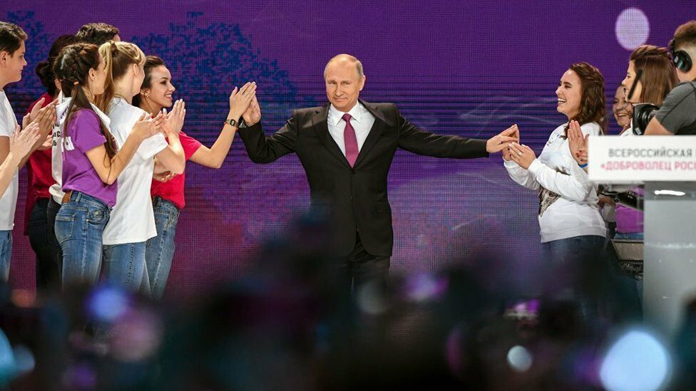 Russian President Vladimir Putin on a stage with women clapping