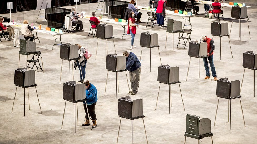 Voters cast their ballot in voting booths