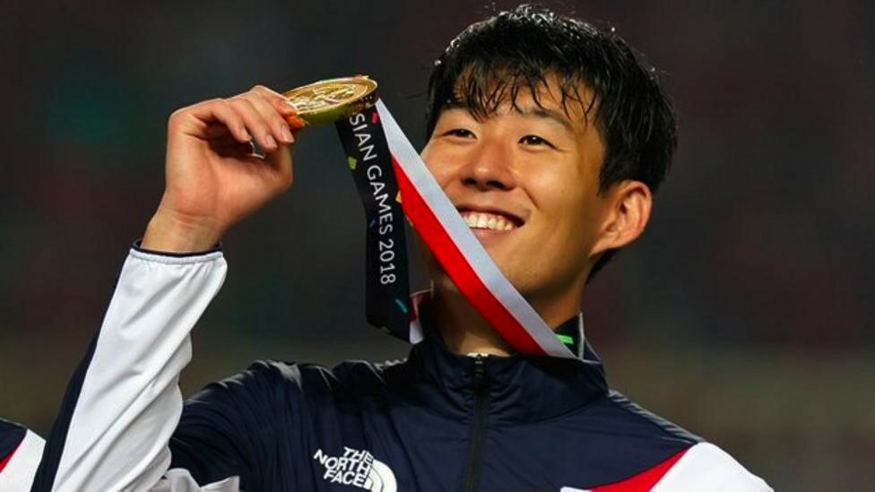 Son Heung-min holds aloft his gold medal,