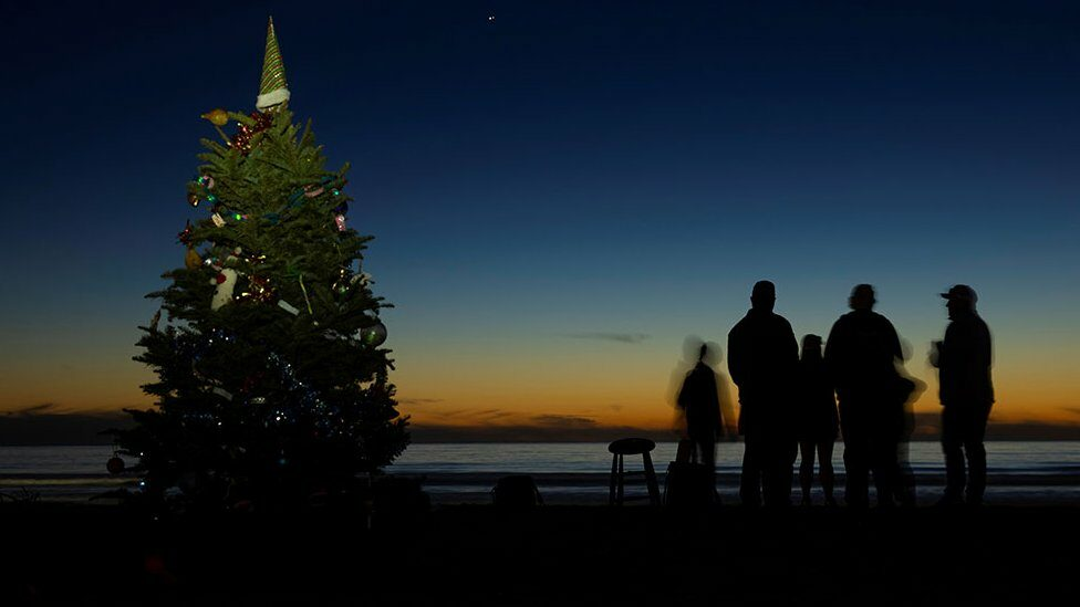 Groups of people gather near a Christmas tree on the beach