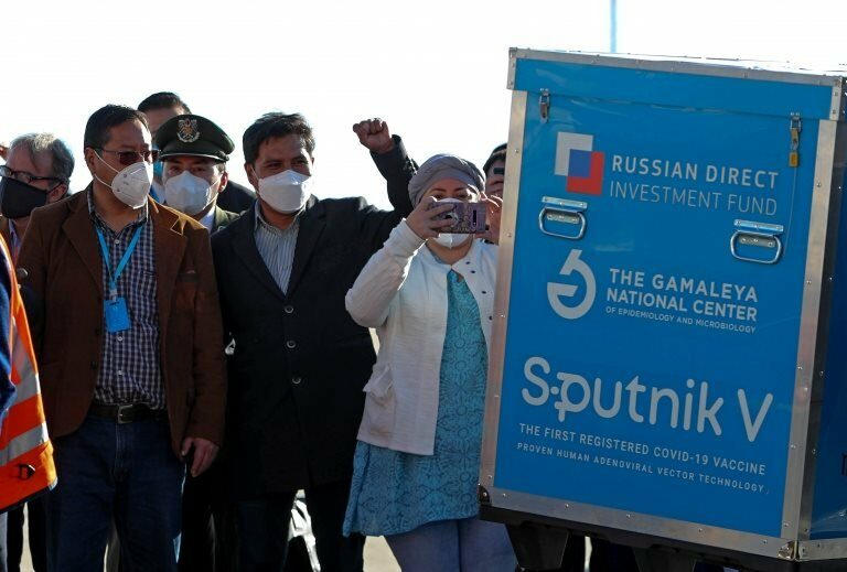 Bolivian President Luis Arce (L) observes a container with doses of Russian vaccine Sputnik V, at International Airport of El Alto, Bolivia, 28 January 2021. Bolivia received the first lot of 20,000 doses of the Sputnik V vaccine
